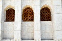 砖墙和一个古老被雕刻的阿拉伯伊斯兰教的伊斯兰教的三角窗口的三个木棕色老前辈的纹理与orname的 图库摄影