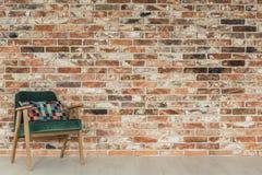 砖墙和绿色扶手椅子 库存照片