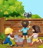绘砖墙的孩子在庭院里 库存图片