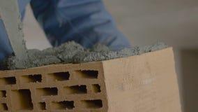 砖墙的建筑 在砖的修平刀传播的水泥 工作者涂砖的水泥 股票录像