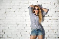 砖墙的时尚街道样式青少年的女孩 免版税图库摄影