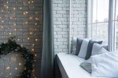 砖墙的设计有一个云杉的花圈和枕头的 库存照片