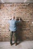 砖墙背景的建筑工人 免版税库存照片
