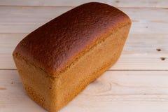 砖布朗酿造了从黑麦面粉的面包,在木书桌上 库存图片