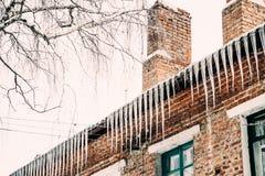 砖房子和冰冰柱 免版税库存图片
