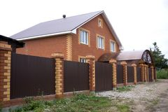 砖房子在有两辆汽车车库的郊区 免版税库存图片
