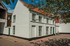 砖房子门面在优美的小的正方形与花和树附近的在布鲁日 库存图片