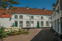 砖房子门面在优美的小的正方形与花和树附近的在布鲁日 库存照片