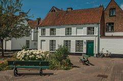 砖房子门面在flowerd附近的与树的一点正方形在布鲁日 免版税库存图片