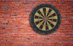 砖掷镖的圆靶墙壁 免版税库存照片