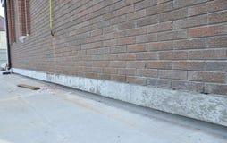 砖有未完成的基础修理和绝缘材料的房子墙壁 免版税库存图片