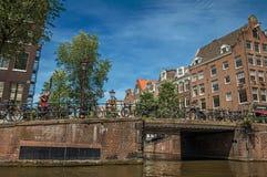 砖瓦房和桥梁在运河有自行车和晴朗的蓝天的在阿姆斯特丹 免版税库存照片