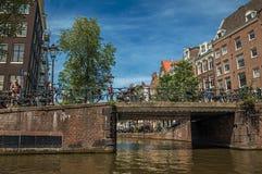 砖瓦房和桥梁在运河有自行车和晴朗的蓝天的在阿姆斯特丹 库存照片