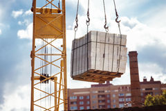 砖起重机举的堆的特写镜头图象在蓝天的 免版税库存图片