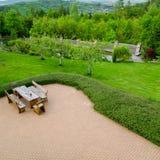 砖铺了有舒适的露台家具的露台有土气扶手椅子的和庭院围拢的一把凳子,大角度看法 图库摄影