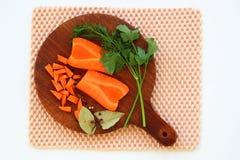 砧板特写镜头用新鲜的红萝卜,绿叶,月桂树le 免版税库存图片