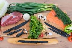 砧板用蕃茄、荷兰芹和牛肉未加工的内圆角黏附了与刀子 免版税库存照片