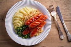 砰然作响物饲料 香肠、土豆泥、绿豆和油煎的葱在白色板材在木桌上 库存照片