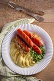 砰然作响物饲料 香肠、土豆泥、绿豆和油煎的葱在白色板材在木桌上 免版税库存照片