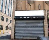 破产事务的被放弃的商店前面  安全门是闭合的 标志说,吹灭销售 免版税图库摄影