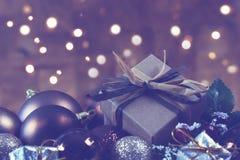 破旧的别致的礼物在与bokeh lig的圣诞节装饰紧贴了 库存图片