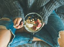 破旧的牛仔裤和毛线衣的妇女吃健康早餐的 免版税图库摄影