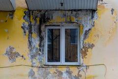 破旧的脏的墙壁,被剥皮的膏药,塑料窗口,贫民区 免版税库存照片