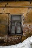 破旧的脏的破裂的墙壁,被打碎的窗口,被放弃的房子,冬天,贫穷概念 免版税库存图片