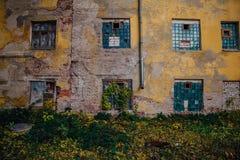 破旧的长满的脏的墙壁,被打碎的窗口,被放弃的房子 免版税库存图片