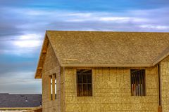 破晓的未完成的家反对多云天空 免版税库存照片