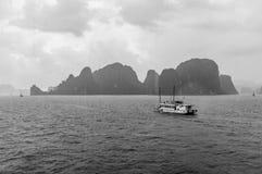 破烂物横跨下龙湾,越南的小船航行 免版税图库摄影