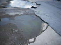 破裂和残破的沥青坑洼用表面上的水  免版税库存照片