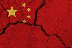 破裂的地球上的中国旗子 免版税图库摄影