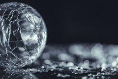 破裂的玻璃与轻的bokeh的球形银色星宏观照片  免版税图库摄影