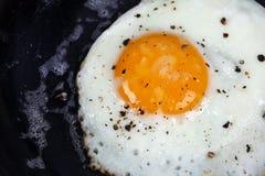 破裂的鸡蛋油煎的有机胡椒盐 库存照片