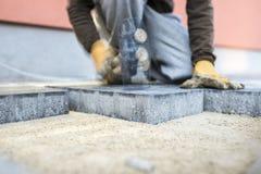 砸紧下来一块新的铺路板或砖与行动迷离的建造者 免版税图库摄影