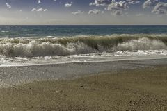 硕大撞入一个pebbled海滩的绿松石和深绿膨胀在一个天空蔚蓝夏日在西西里岛 免版税库存图片