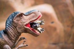 硕大暴龙捉住在岩石山前面的更小的恐龙 免版税库存图片