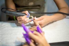 硬件修指甲 老胶凝体油漆撤除在沙龙的 客户的修指甲主要做的秀丽做法,特写镜头和上面竞争 免版税库存照片