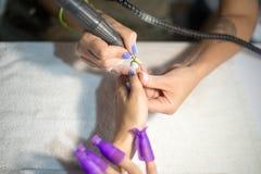 硬件修指甲 老胶凝体油漆撤除在沙龙的 客户的修指甲主要做的秀丽做法,特写镜头和上面竞争 库存图片