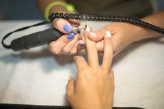 硬件修指甲 老胶凝体油漆撤除在沙龙的 客户的修指甲主要做的秀丽做法,特写镜头和上面竞争 免版税库存图片