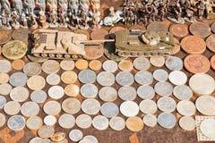 硬币、小锡兵和坦克待售在跳蚤市场上 库存图片