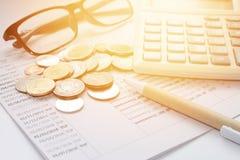硬币、泰国金钱、笔、计算器、玻璃和储蓄帐户存款簿在白色背景 免版税图库摄影