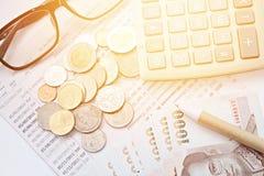 硬币、泰国金钱、笔、计算器、玻璃和储蓄帐户存款簿在白色背景 库存照片