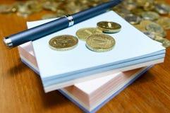 硬币、笔和纸 免版税库存照片