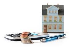硬币、计算器和笔在一个被弄脏的房子模型前面, cal 库存图片
