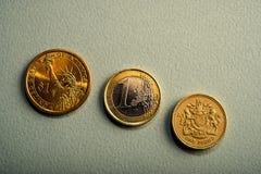 硬币一美元,一欧元,在桃红色背景的一磅 免版税库存图片