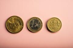 硬币一美元,一欧元,在桃红色背景的一磅 免版税图库摄影