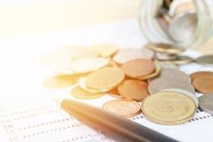 硬币从玻璃瓶子和笔驱散了在储蓄存款书或财政决算 图库摄影