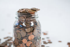 硬币充分的玻璃瓶子 免版税库存照片